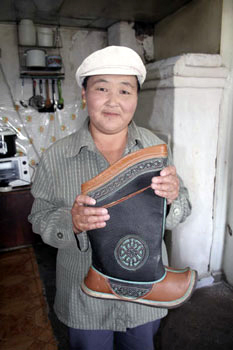 Lady holding a pair of hand-made Mongolian Boots