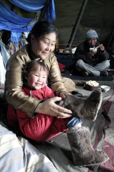 picture of old lady helping child wear Mongolian Boots