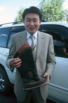 Special deilvery of hand-made boots by young man in western style suit